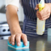 Man cleaning a counter with a sponge.