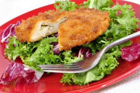 Stuffed, breaded chicken breast on a bed of lettuce.