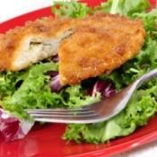 Stuffed, breaded chicken breast on a bed of lettuce.