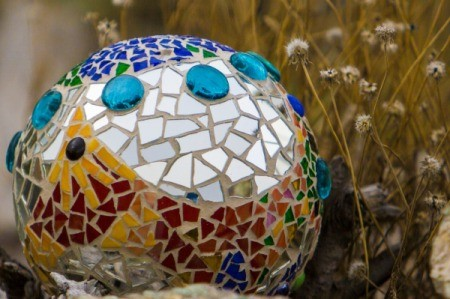 Mosaic covered bowling ball outside.