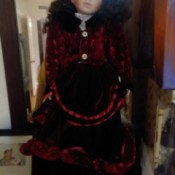 Value of an Ashley Belle Collection Porcelain Doll - doll wearing a deep red velvet outfit