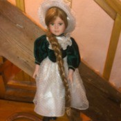 Value of a Porcelain Doll - doll wearing a green velvet bodice dress with a white lace skirt and matching hat