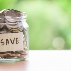 """Jar full of coins with the word """"save"""" on the outside."""