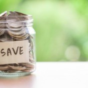 "Jar full of coins with the word ""save"" on the outside."