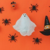 Gauze ghost on orange surrounded by spiders.