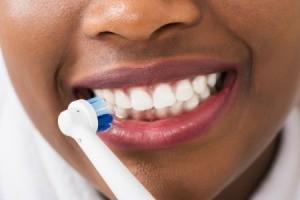 Woman brushing her white teeth.