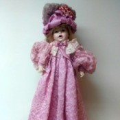 Identifying a Porcelain Doll - doll wearing a long pink dress and matching hat