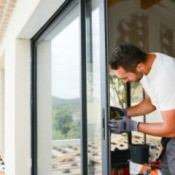 Man working on a sliding glass door.