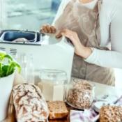 Woman making bread in a bread machine.