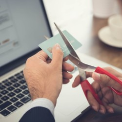 A man cutting up his credit cards.