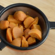 A strainer with canned yams.