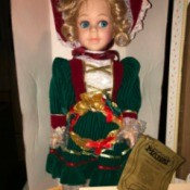 Value of a Seymour Mann Doll - blond doll wearing a green dress with crimson detail