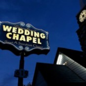 A neon Graceland wedding chapel sign next to a chapel.