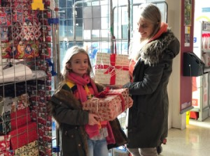 A mother and child choosing gifts from a donation site.