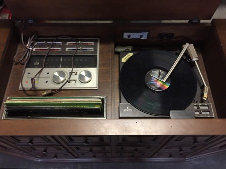 Turntable and controls for a vintage zenith console stereo system.