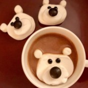 Marshmallow Polar Bears - two finished bears next to a cup of chocolate with a floating, melting polar bear