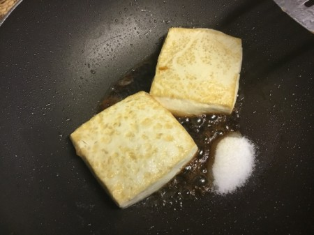adding sugar and soy sauce to pan