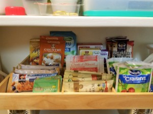 A shadowbox frame storing small packets in a pantry.