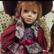 Identifying a Porcelain Doll - doll wearing wine colored dress and matching hat with a floral vest