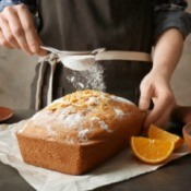 sprinkling powdered sugar on a loaf cake