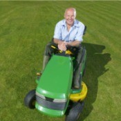 man sitting on a green and yellow riding mower