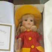 Value of a Heritage Signature Collection Porcelain Doll - doll wearing a red and yellow raincoat