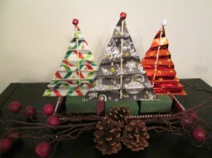 Making Accordion Christmas Trees - three finished trees with a tiny ball ornament on top, and pine cones and other decorations in front