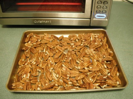Pecans spread on baking sheet