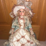 Identifying a Porcelain Doll- doll wearing an elaborate pink dress with jacket