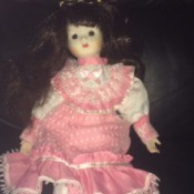 Identifying a Porcelain Doll - dark haired doll wearing a pink dress