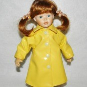 Value of a Cracker Barrel Porcelain Doll - red haired doll wearing a yellow rain coat and boots