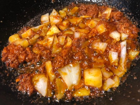adding onion to Chorizo in pan