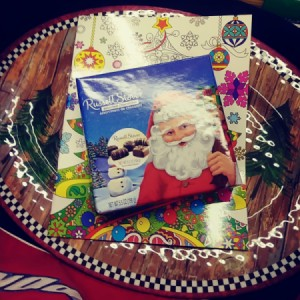 A seasonal tray with a coloring book and a box of chocolates.