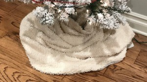 A blanket being used as a Christmas tree skirt.