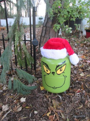 Helium Tank Upcycled as The Grinch - Grinch sitting on the ground outside