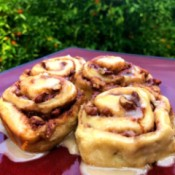 Orange Pecan Cinnamon Rolls on table by orange tree