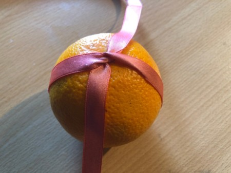 How to Make Orange Clove Pomanders - place orange in the center of the ribbon and tie a knot