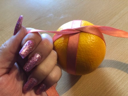 How to Make Orange Clove Pomanders - wrap the other way around like a present and tie another knot tightly on the other side