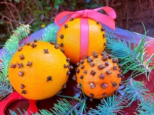 How to Make Orange Clove Pomanders - three variations resting on a bed of evergreen branches