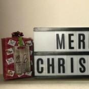 Giftbox Christmas Countdown Calendar - calendar sitting on a shelf with the Merry Christmas sign and the doily tree sign