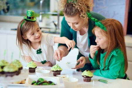 2 girls and a woman wearing green, decorating green cupcakes.