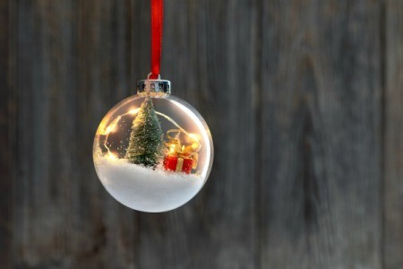 Clear Christmas ornament filled with tree, snow and a present.