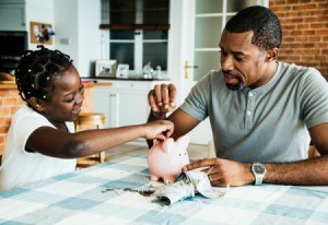 Father and daughter putting money in a piggy bank.