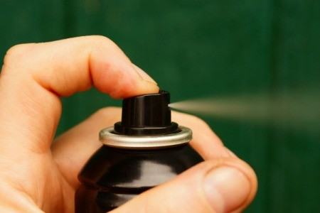 Hand spraying hairspray.