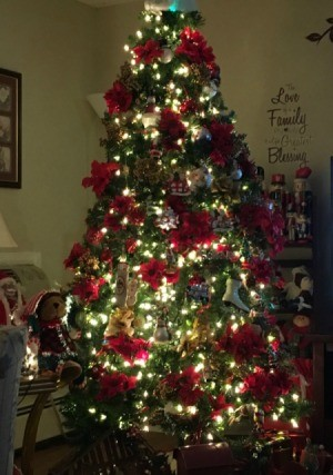 An artificial Christmas tree decorated with poinsettias and white lights.