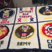 A large crocheted wall hanging with a military theme.