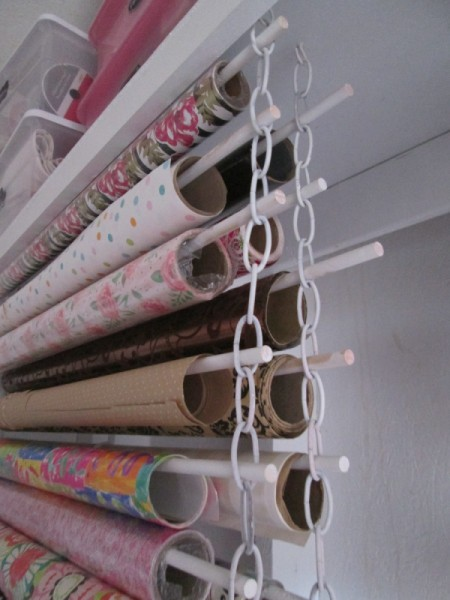 Rolls of wrapping paper stored on dowels suspended by metal chains.