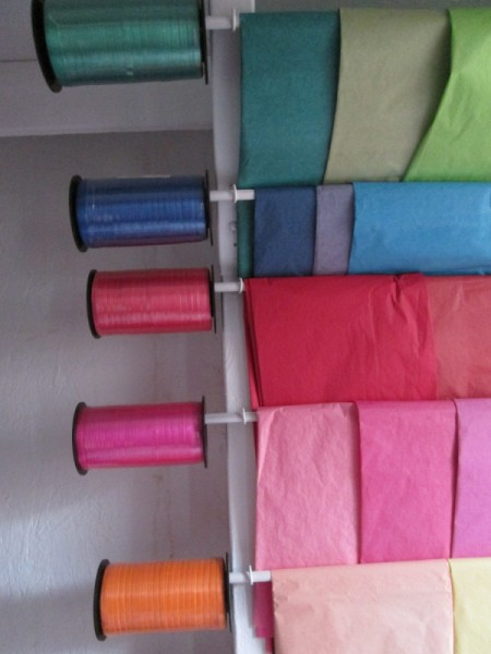Ribbon and tissue paper stored on dowels suspended by metal chains.