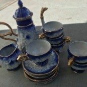 Identifying a China Coffee Set - tall tea pot with cups and saucers, relief decorations of cherubs, gold trim