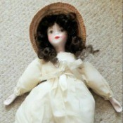 Identifying a Porcelain Doll - doll wearing a period long white dress and a straw hat